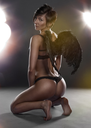 Beautiful woman in angel wings and lingerie kneeling on the floor facing away from the camera displaying her curvy toned bare bottom and the feathery wings as she looks back at the camera photo