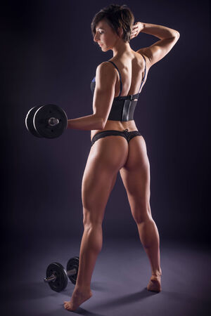 Muscular beautiful young athletic woman in lingerie working out with weights standing with her back to the camera on tip toe sculpting the muscles in her toned sexy body Stock Photo