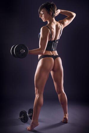 levantar pesas: Muscular mujer atlética joven hermosa en la ropa interior que trabaja con pesas de pie con su espalda a la cámara de puntillas esculpir los músculos de su tonificado cuerpo sexy Foto de archivo