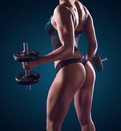physique: Dark portrait of the torso of a fit muscular athletic woman working out with weights in lingerie showing off her physique and firm buttocks Stock Photo