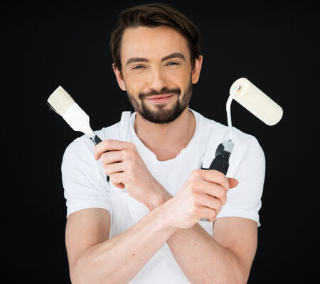 qualified worker: Smiling handsome young male painter with a beard holding a roller and brush in his crossed arms on a dark background