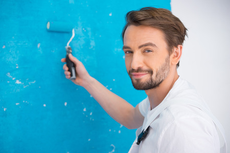 qualified worker: Attractive bearded young painter in dungarees standing looking at the camera holding up a roller on a bluish background Stock Photo