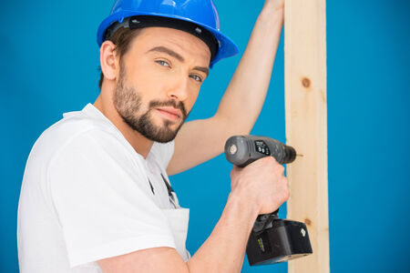 power operated: Carpenter or builder wearing a hardhat standing in front of a blue wall drilling a hole in a plank of wood with a handheld battery-operated drill Stock Photo