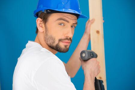 quizzical: Constructor usando un taladro en un tabl�n de madera de inflexi�n y mirando a la c�mara con una expresi�n seria interrogante Foto de archivo