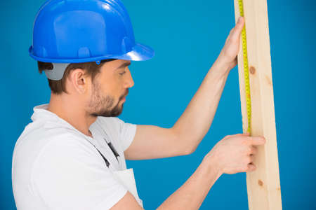 power operated: Carpenter or builder wearing a hardhat concentrating as he measures a plank of wood with a tape measure, blue background