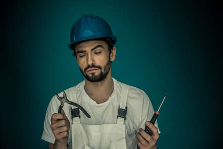 decides: Attractive bearded young workman standing eyeing his tools holding up a pair pf pliers and a screwdriver as he decides which is best to use Stock Photo