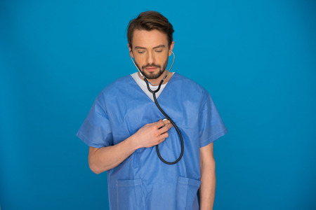 Attractive male doctor wearing a stethoscope and theatre gown standing staring thoughtfully at the floor against a blue background with copyspace photo