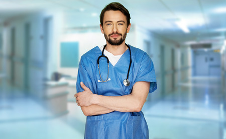 hospital gown: Confident young doctor in a hospital foyer standing in a surgical gown and stethoscope smiling at the camera with folded arms