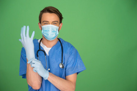 Young male doctor wearing a mask, gown and stethoscope putting on surgical gloves on a green background with copyspace