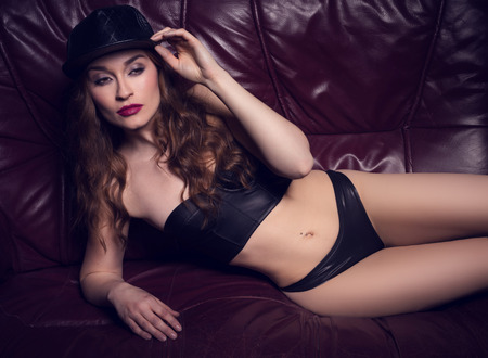 sexy woman with red hair wearing leather lingerie and hat photo