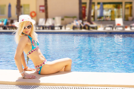 suncare: cute blonde woman by the swimming pool resort