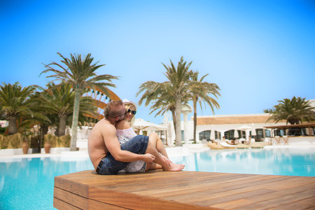suncare: cute couple kissing near residence with swimming pool