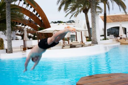 suncare: man jumping in to the water near residence with swimming pool
