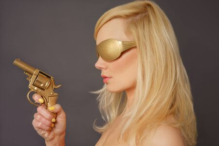 armed: Side view of a Blonde Lady Holding a Golden Gun. Stock Photo