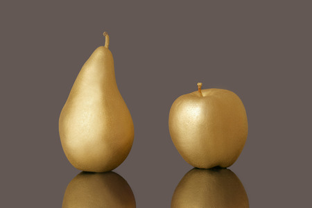 valuable: Golden pear and apple on dark background. Stock Photo