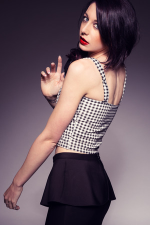 sleeveless top: Beautiful woman with red lips wearing sleeveless top on dark background