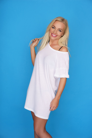 warm shirt: Beautiful happy young blond woman in a loose white summer shirt posing sideways looking at the camera with a lovely warm friendly smile, on a blue background