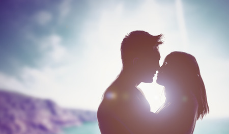Silhouettes of a loving couple backlit by a bright sun in an intimate embrace staring into each others eyes as they prepare to kiss, mountain backdrop with copyspace