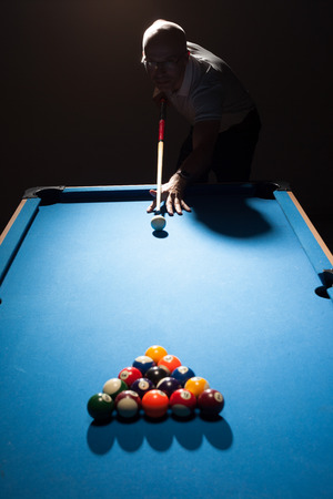 shadowy: Man playing a game of pool lining up as the break shooter as he takes aim with his cue and ball at the triangular formation of object balls in a dark shadowy pub or bar
