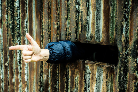 criminality: Hand out of a rusty wall showing the finger gun gesture, concept of violence, conflicts, war or criminality in poor countries or suburbs