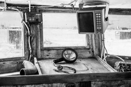 Interior of an old cockpit on a fishing boat with navigation equipment and o portable spotlight lying on the counter in black and white vintage style
