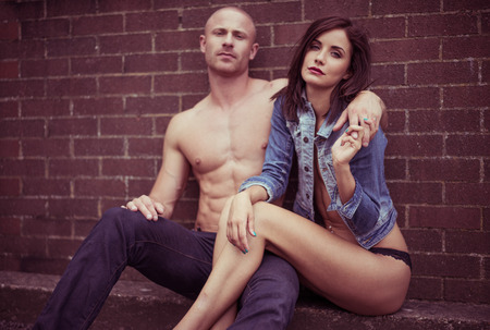 half naked: Half naked sweet couple sitting on the floor in front of brick wall Stock Photo