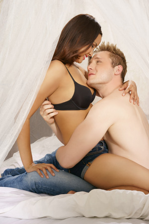 sexy couple in bed: Loving couple sitting on a bed in a close embrace with the woman on her partners lap smiling down affectionately into his eyes Stock Photo