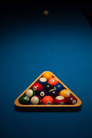 eightball: Racked set of numbered object pool balls in a triangular wooden rack ready for an eight-ball frame or game on a blue beize table with copyspace