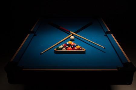 Einsatzzeichen: Pool Ausr�stung bereit f�r ein Spiel mit gekreuzten Holz Cues, zerbrach Kugeln und einem Spielball auf einem blauen Tuch Tisch umgeben von Dunkelheit