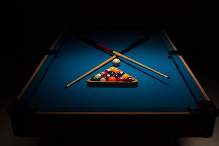 pool cues: Pool equipment ready for a game with crossed wooden cues, racked balls and a cue ball on a blue baize table surrounded by darkness
