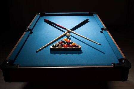 cues: Pool equipment ready for a frame with crossed wooden cues, racked balls and a cue ball on a blue baize table surrounded by darkness Stock Photo