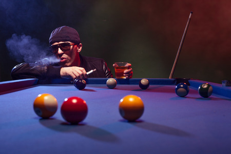 shadowy: Man in sunglasses and a cap playing pool in a shadowy nightclub standing surveying the lay of the balls on the table smoking e-cigarette or e-shisha