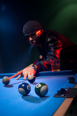 pool cue: Trendy man in dark glasses and a cap playing pool lining up on the cue ball with his cue as he prepares to shoot in a dark pub or club