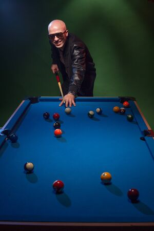 lining up: Trendy man in dark glasses and a cap playing pool lining up on the cue ball with his cue as he prepares to shoot in a dark pub or club