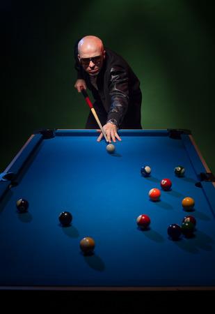 hombre disparando: Hombre de moda en gafas de sol y una piscina en el casquillo de juego haciendo cola en la bola blanca con el taco, mientras se prepara para disparar en un bar oscuro o club Foto de archivo