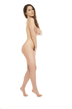 female nudity: Full length portrait of a beautiful woman posing nude standing sideways on her tip toes shielding her nipples and pubic area with her hands while turning to smile at the camera, isolated on white Stock Photo