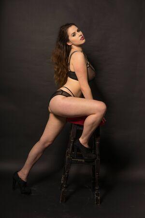 ravishing: Sexy woman in her underwear seductively posing with stool on dark background Stock Photo