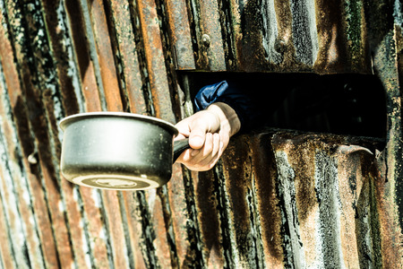 waiting convict: Hand out of a narrow opening in a rusty old wall holding a cooking pot, concept of captivity, quarantine, world hunger and poverty Stock Photo