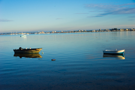 dinghies: Scenic view of two moored small wooden motor boats or dinghies on a calm sea with their reflections mirrored on the still water and a coastline visible in the distance