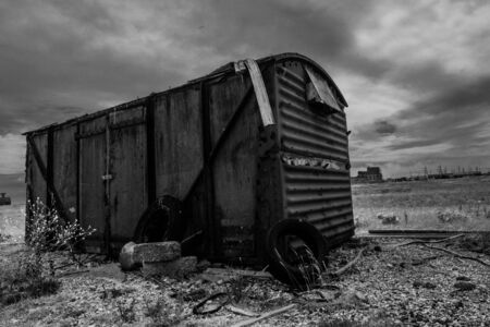 barrack: Dramatic black and white image of an old fishing hut, on a deserted and desolated beach, under a cloudy sky Stock Photo