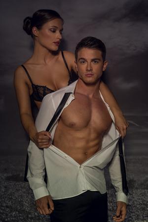 parejas sensuales: Mujer atractiva rasga la camisa del hombre desde atrás exponiendo musculoso pecho