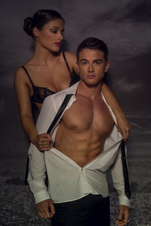 lustful: Sexy woman rips shirt of man from behind exposing muscular chest