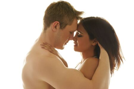 sexualidad: Amar a dos jóvenes que abraza blando tocar frentes y narices, la cabeza y los hombros vista de perfil en blanco Foto de archivo