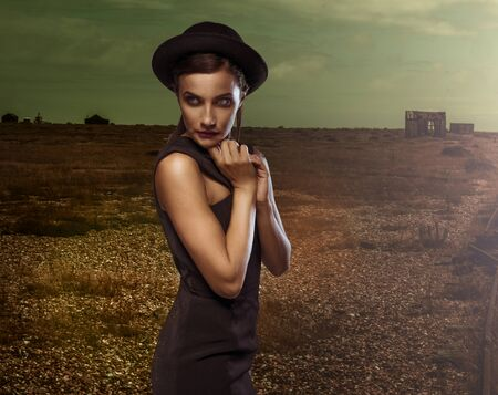 downcast: Demure elegant young woman in a stylish hat and dress posing with downcast eyes and her hands raised to her chim in a gloomy atmospheric landscape Stock Photo