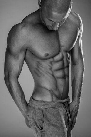 sixpack: Handsome muscular man shirtless wearing grey pants Stock Photo