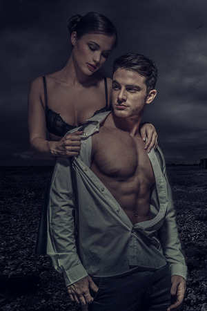 seduction: Sexy Young Couple Fashion Photo, Isolated Dark Gloomy Background Stock Photo