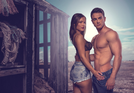 trendy: Fashion Photo Shoot. Two Sexy Couple Posing Flaunting Perfect Body Beside Old Wooden House
