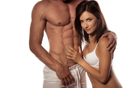 erotic couple: Pretty Hot Woman Seductively Looking at Camera White Touching Partners Perfect Abs, Isolated on White.