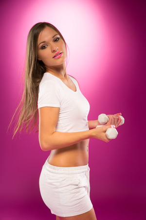 body curve: Young Sexy Woman in White Sports Attire Side View Portrait with Barbells, Isolated Violet. Showing Perfect Body Curve