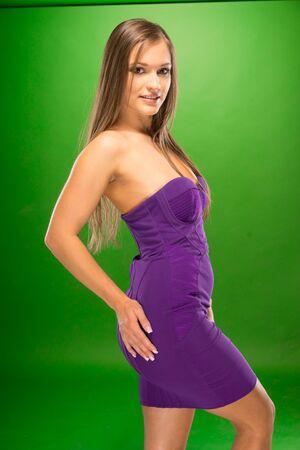 emphasising: Giovane donna in molto sexy vestito viola Vista laterale Pose, Isolato Sfondo verde. Sottolineando curve del corpo e linee Archivio Fotografico